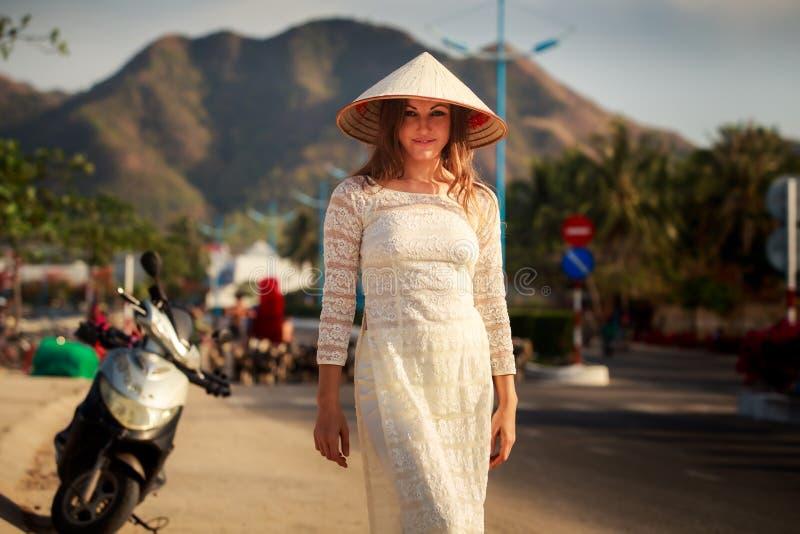 la muchacha en vietnamita se viste y el sombrero sonríe en vespa fotografía de archivo
