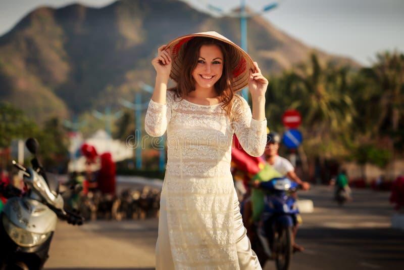 la muchacha en vietnamita viste el sombrero de los tactos contra las vespas defocused fotos de archivo