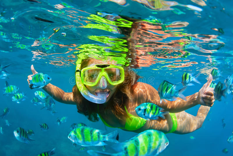 La muchacha en zambullida de la máscara que bucea bajo el agua con el arrecife de coral pesca imágenes de archivo libres de regalías