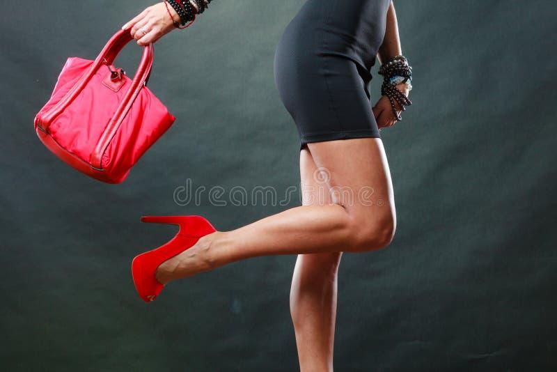 La muchacha en zapatos claveteados rojos del vestido del cortocircuito del negro sostiene el bolso foto de archivo