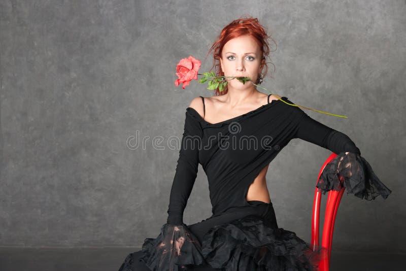 La muchacha encantadora con una rosa roja
