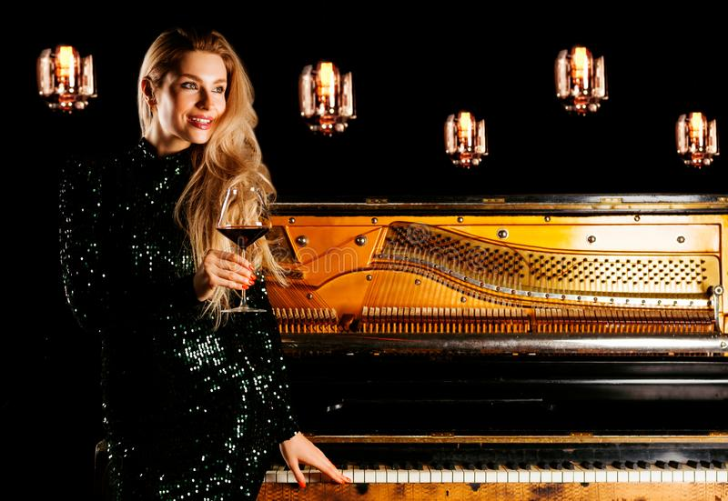 La muchacha encantadora en vestido de noche se sienta en el piano y las actitudes para la cámara con una copa de vino fotos de archivo