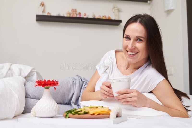 La muchacha encantadora que miente en cama desayuna su romántico imagenes de archivo