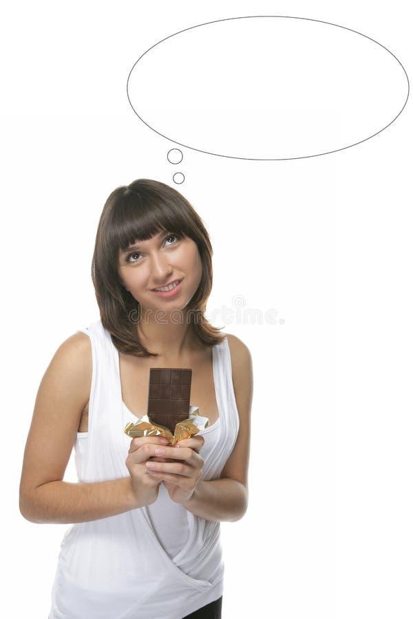 La muchacha encantadora sostiene un chocolate foto de archivo libre de regalías