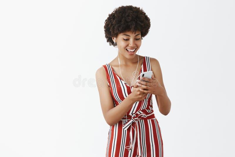 La muchacha encontró la gran canción que hace juego su humor Afroamericano encantador contento y satisfecho en guardapolvos rayad imagen de archivo