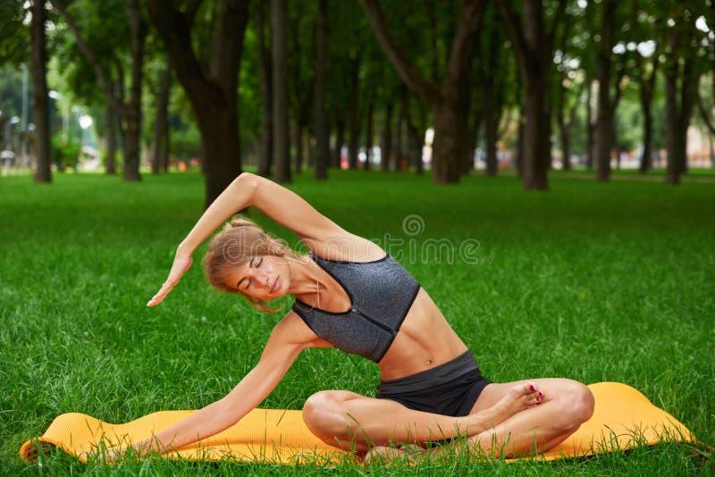 La muchacha enganchó en aptitud y gimnasia en el parque fotografía de archivo
