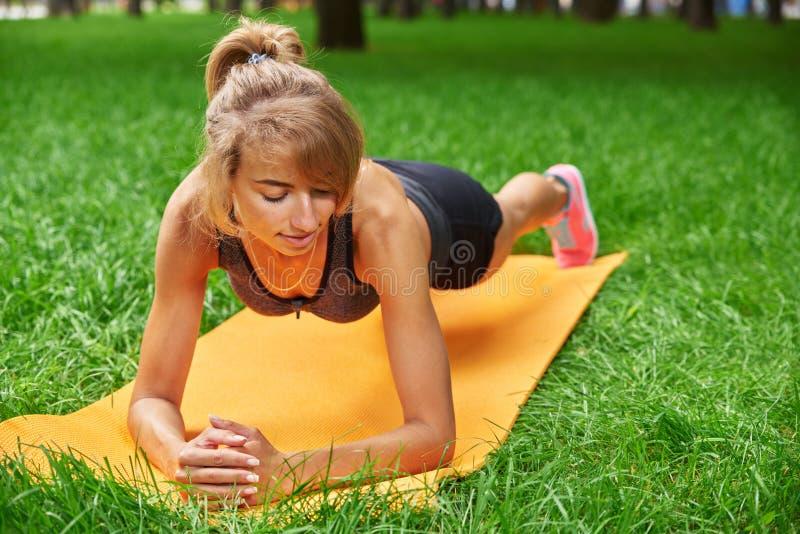La muchacha enganchó en aptitud y gimnasia en el parque imagen de archivo