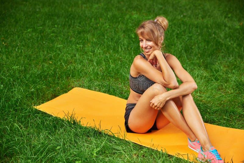La muchacha enganchó en aptitud y gimnasia en el parque fotos de archivo