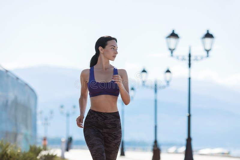 La muchacha entra para los deportes, corre por la mañana a lo largo de la 'promenade' por el mar imagenes de archivo