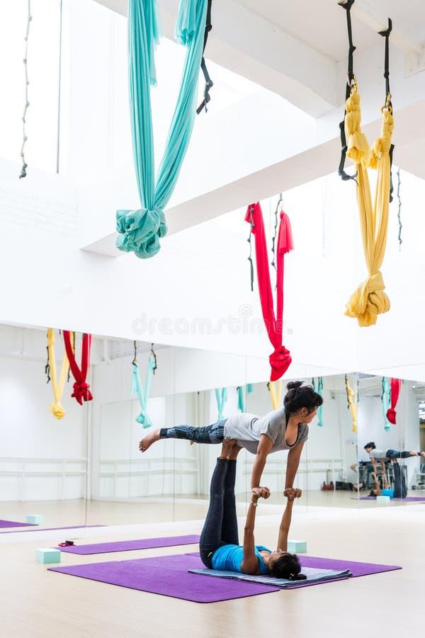 La muchacha entrenó a estiramiento de la yoga de cerca por el profesor de la yoga en el estudio de la yoga en Bangkok, Tailandia imagenes de archivo