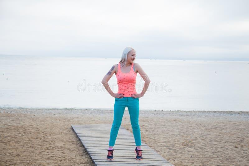 La muchacha es aptitud dedicada en la playa foto de archivo