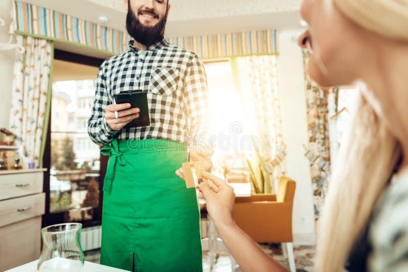 La muchacha es camarero calculado de la tarjeta de crédito en café imágenes de archivo libres de regalías
