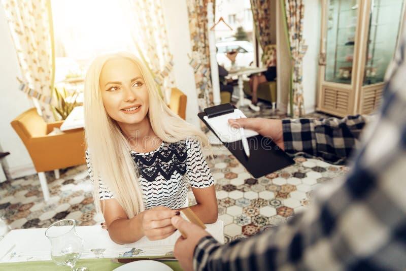 La muchacha es camarero calculado de la tarjeta de crédito en café imagen de archivo