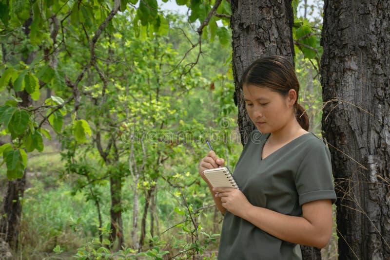 La muchacha es colocación, tomando notas en un pequeño cuaderno en el bosque verde foto de archivo libre de regalías