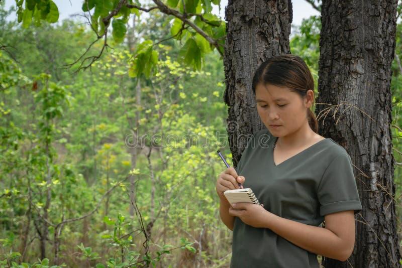 La muchacha es colocación, tomando notas en un pequeño cuaderno en el bosque verde imagenes de archivo