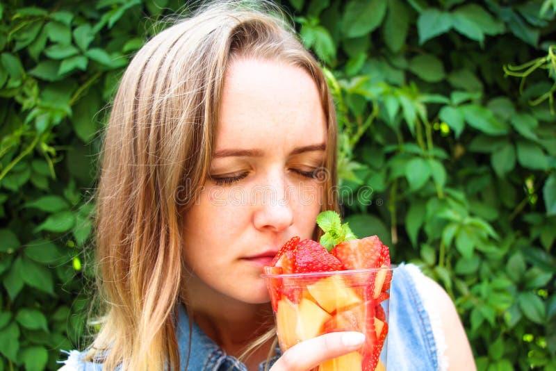 La muchacha es feliz de respirar en el aroma de las frutas frescas que se cortan en pedazos y ponen en un envase imágenes de archivo libres de regalías