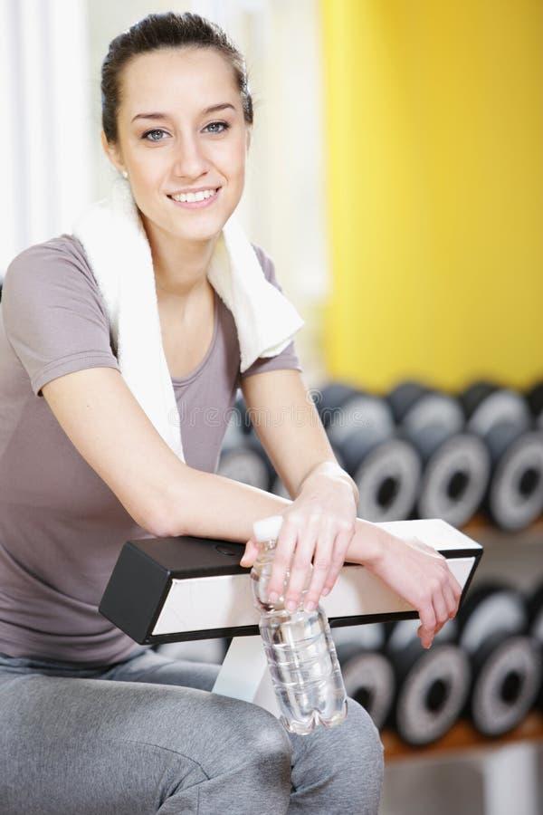 La muchacha es sonriente y de reclinación en una gimnasia. fotos de archivo libres de regalías