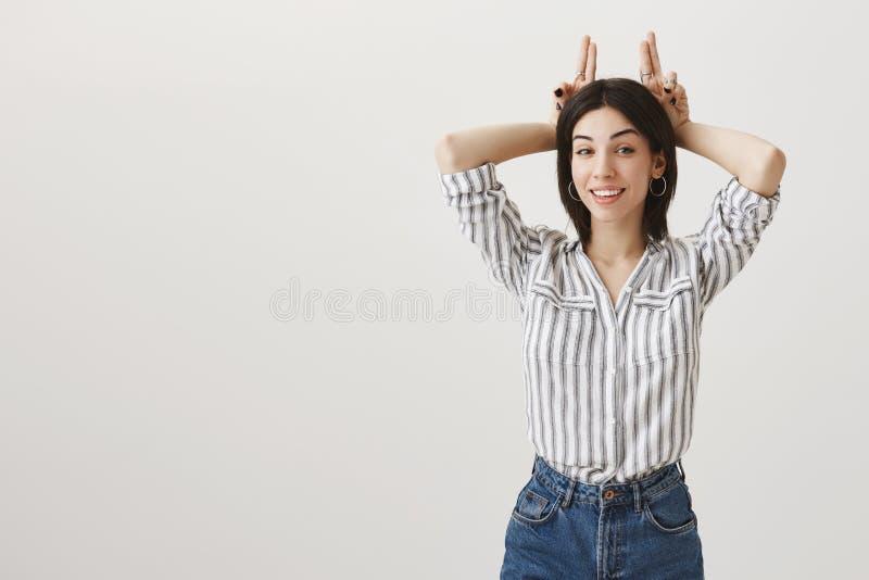 La muchacha es todos los oídos para oír sus nuevas excusas Mujer caucásica femenina de moda con el pelo oscuro que sonríe y que c imagen de archivo