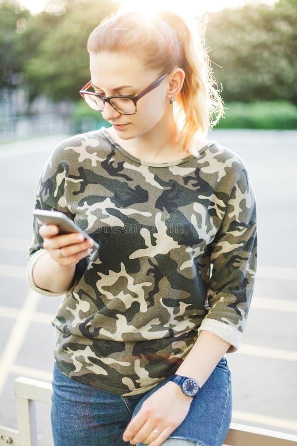 La muchacha escribe el mensaje usando móvil fotos de archivo libres de regalías