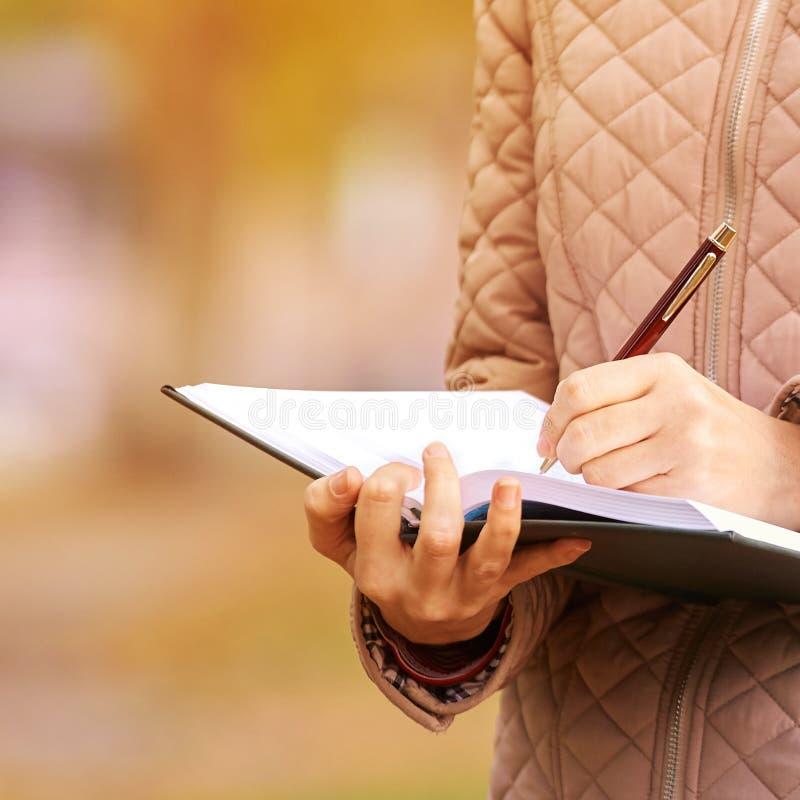 La muchacha escribe el poema en el cuaderno Idea del concepto del negocio Educación de la señora imagenes de archivo