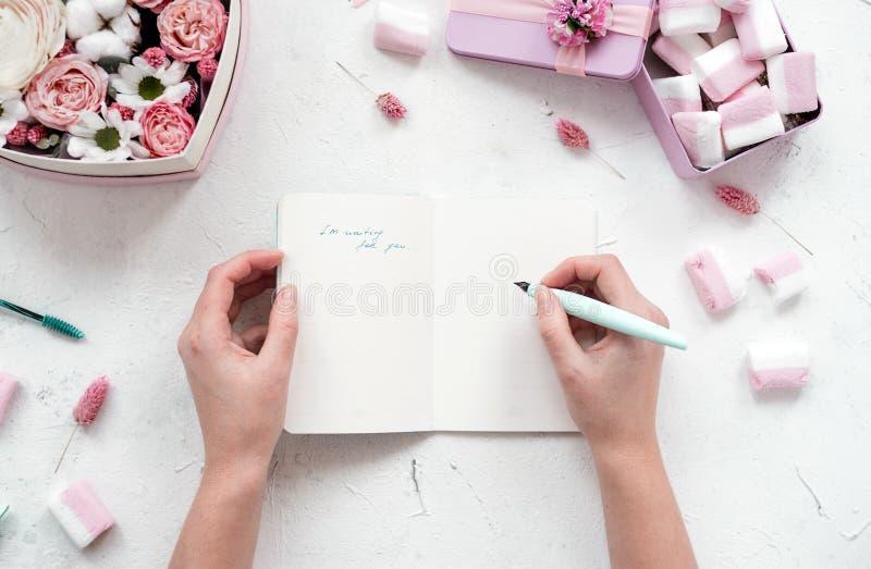 La muchacha escribe en cuaderno abierto en la tabla con las flores y las melcochas, colores en colores pastel Endecha plana de la foto de archivo libre de regalías