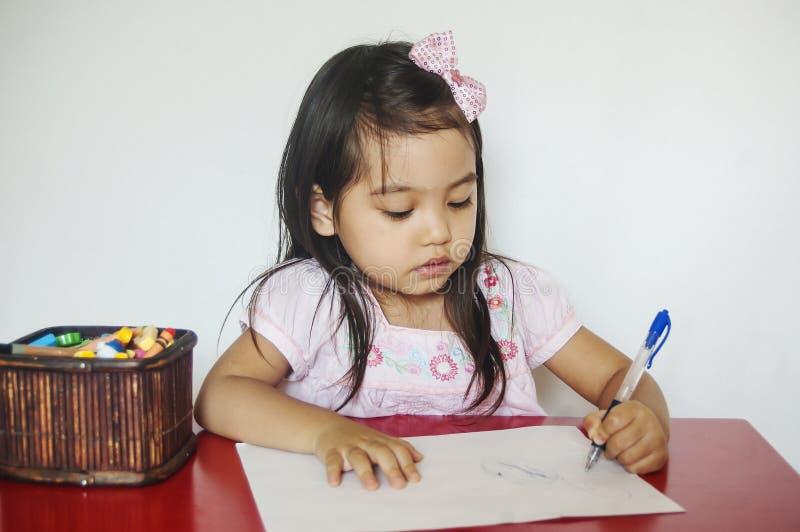 La muchacha escribe en el papel imagen de archivo