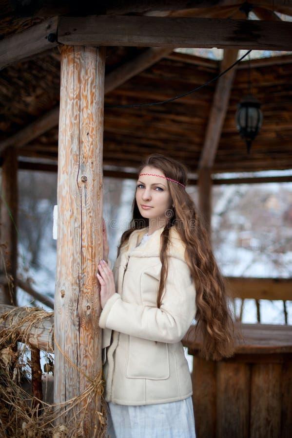 La muchacha eslava hermosa joven con el pelo largo y el vestido étnico eslavo se coloca en un gazebo étnico de madera imágenes de archivo libres de regalías