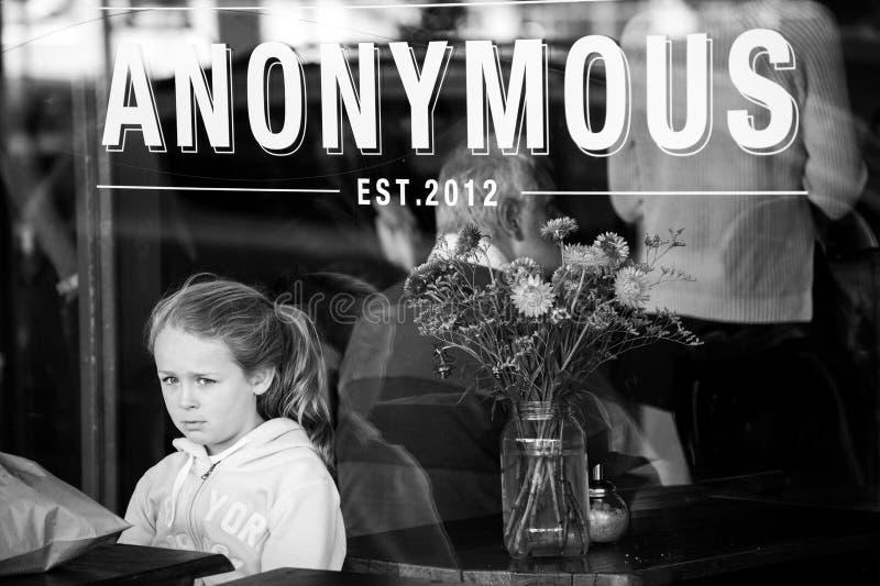 La muchacha espera orden solamente en un café que parece triste y solo imagen de archivo libre de regalías