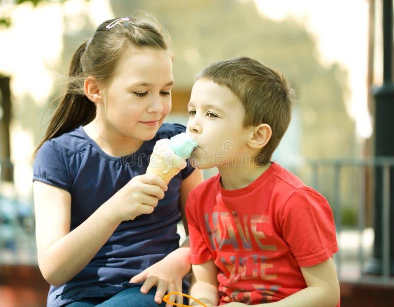 La muchacha está alimentando a su pequeño hermano con helado foto de archivo