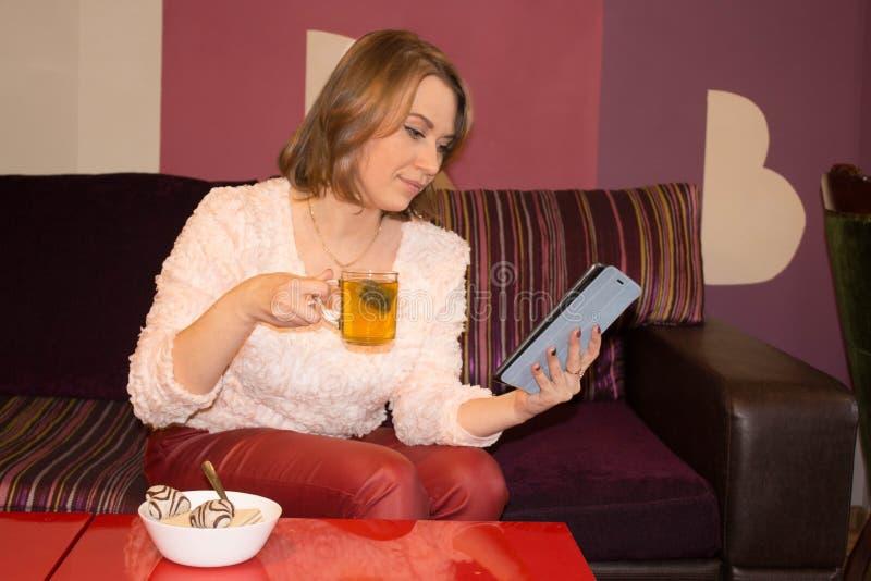 La muchacha está bebiendo té y trabaja con un cojín imagenes de archivo