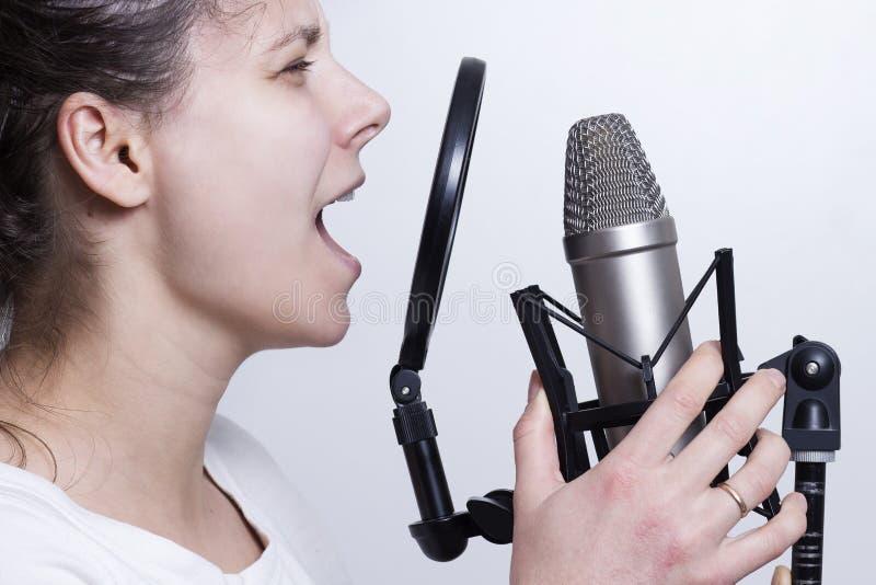 La muchacha está cantando en el micrófono del estudio Registración de la pieza vocal de un cantante joven fotos de archivo