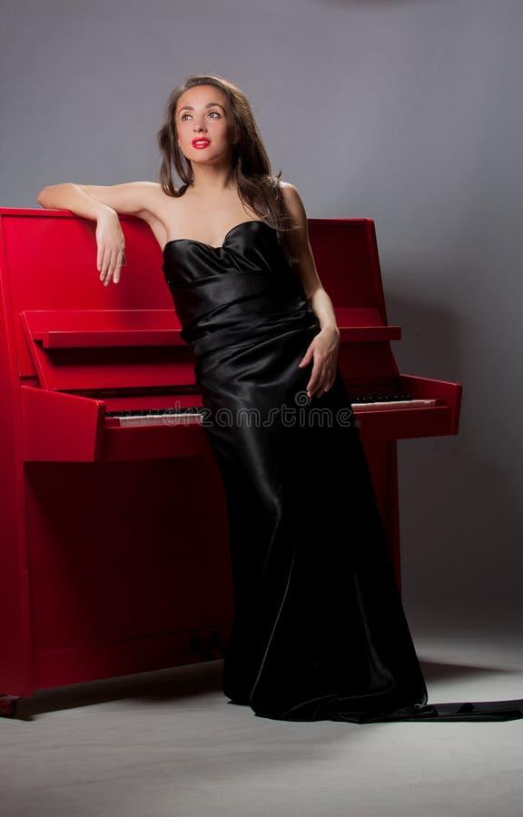 La muchacha está cerca del piano imágenes de archivo libres de regalías