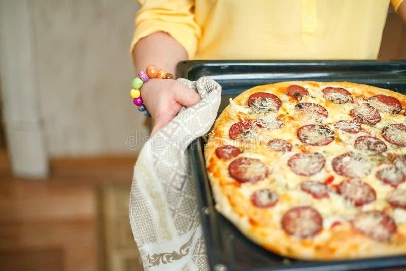 La muchacha está cocinando la pizza foto de archivo