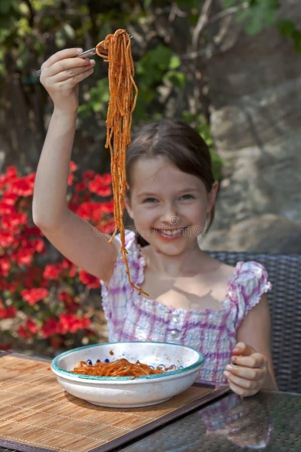 La muchacha está comiendo el espagueti foto de archivo libre de regalías