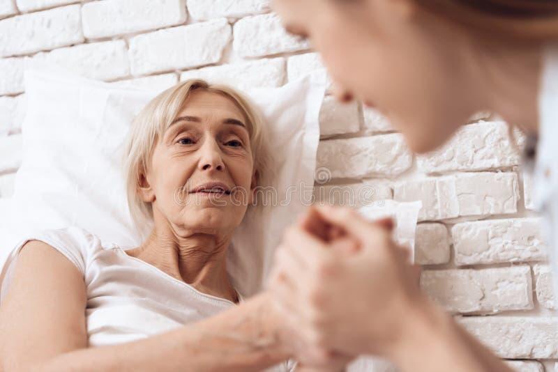 La muchacha está cuidando a la mujer mayor en casa Están llevando a cabo las manos, felices imagenes de archivo