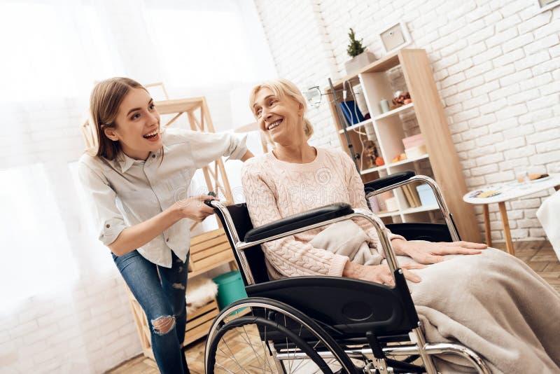 La muchacha está cuidando a la mujer mayor en casa La muchacha está montando a la mujer en silla de ruedas imágenes de archivo libres de regalías
