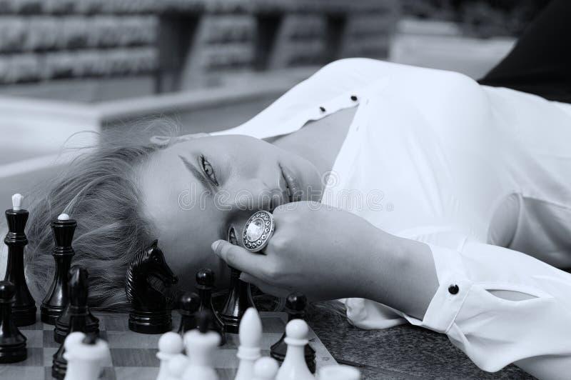 La muchacha está descansando su cabeza en un tablero de ajedrez fotos de archivo