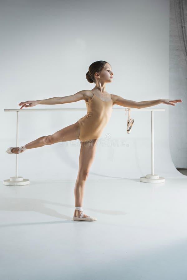 La muchacha está entrenando cerca de la barra del ballet imagen de archivo