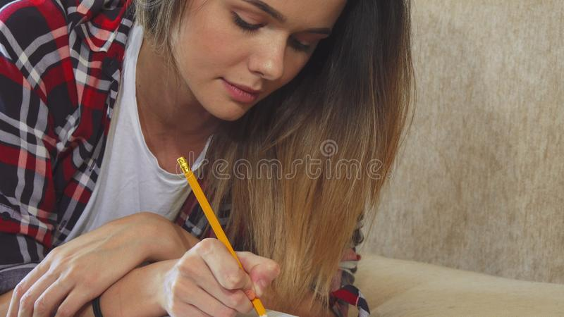 La muchacha está escribiendo en su cuaderno foto de archivo