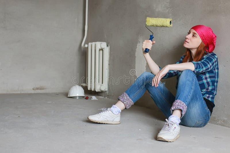 La muchacha está haciendo reparaciones en el apartamento Mudanza casera a un nuevo apartamento El trabajador repara, enyesada y imagen de archivo libre de regalías