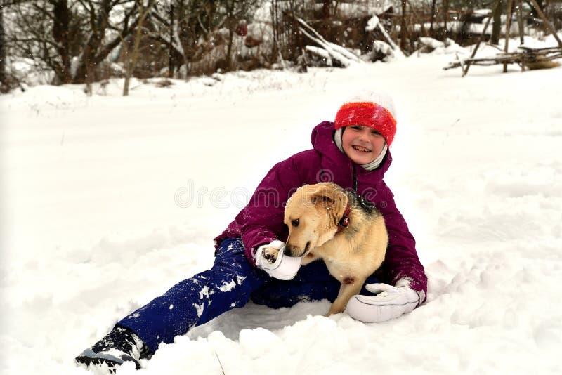 La muchacha está jugando con el perro en la nieve y le da un beso fotografía de archivo