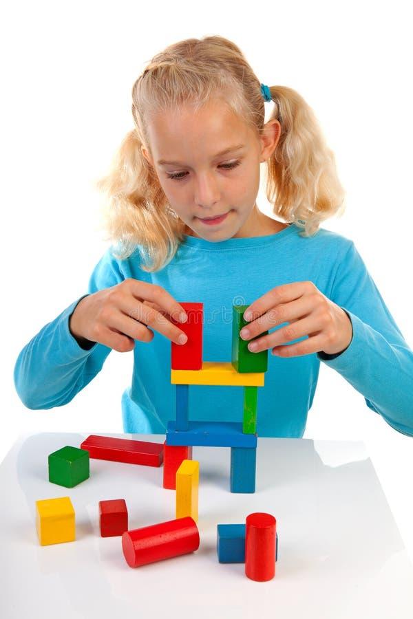 La muchacha está jugando con los bloques de madera coloridos fotos de archivo libres de regalías