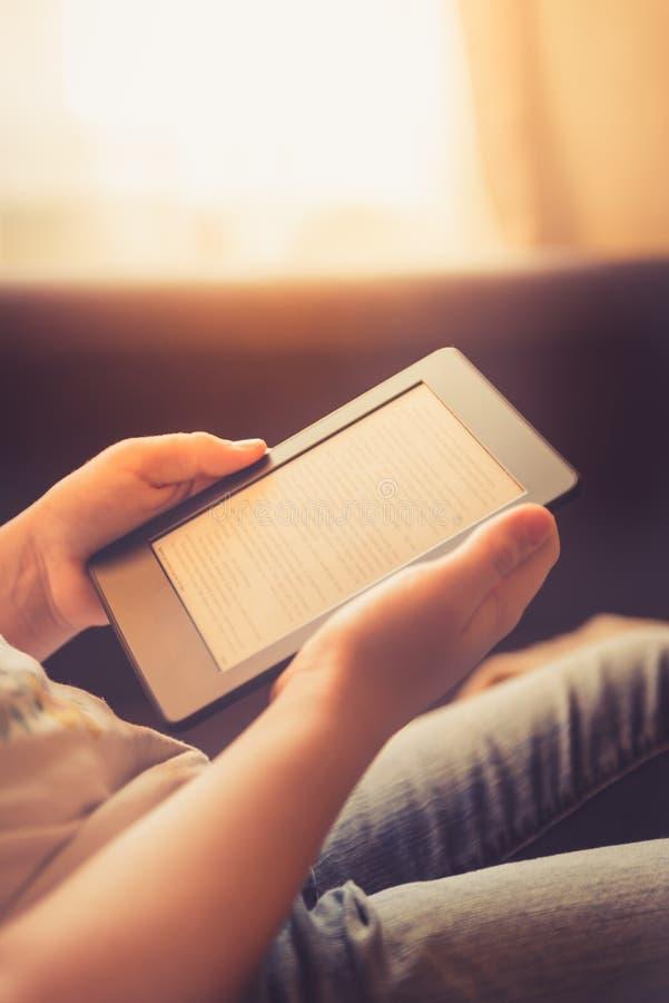 La muchacha está leyendo el ebook en el dispositivo digital de la tableta fotos de archivo
