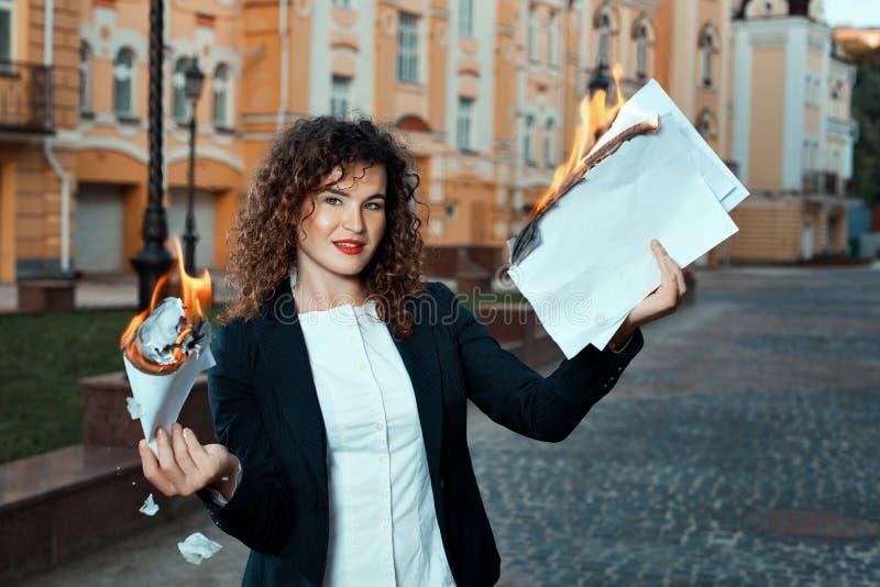 La muchacha está llevando a cabo los documentos que queman fotos de archivo
