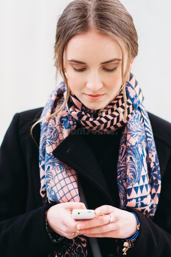 La muchacha está mecanografiando SMS usando el teléfono móvil imagen de archivo
