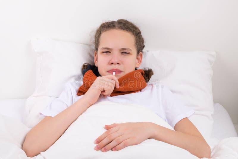 La muchacha está midiendo la temperatura con un termómetro en su boca, mintiendo en cama fotos de archivo