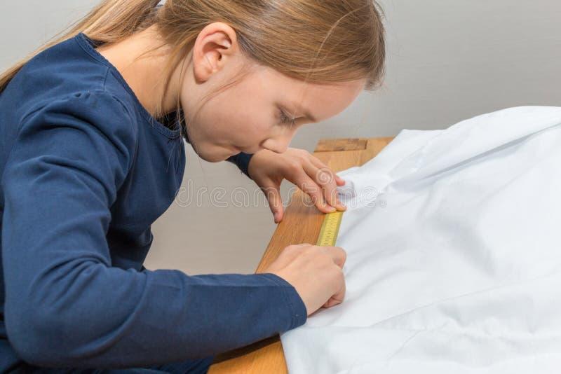 La muchacha está midiendo un textil blanco con una cinta métrica amarilla foto de archivo libre de regalías
