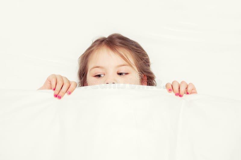 La muchacha está mintiendo en el sofá en el dormitorio y el hersel cubierto foto de archivo