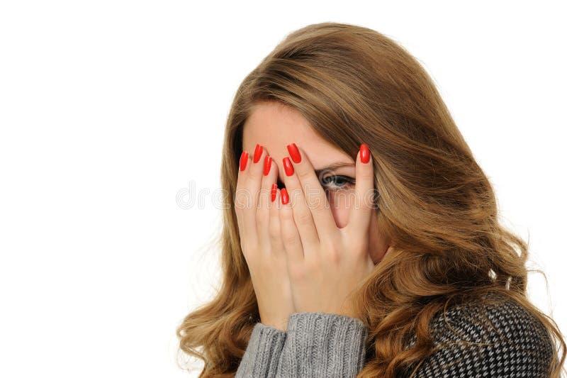 La muchacha está mirando a través de sus dedos fotografía de archivo libre de regalías