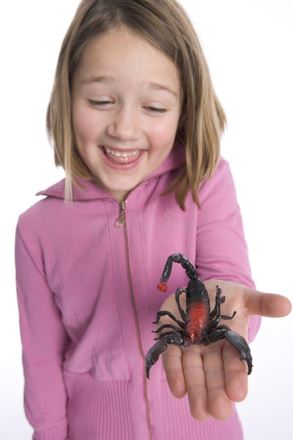 La muchacha está mostrando un escorpión plástico imagen de archivo